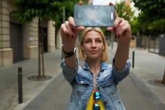 Stilvoller weiblicher Hippie, der ein Foto von am intelligenten Telefon macht Stockfoto