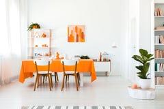 Stilvolles aber einfaches Esszimmer in der klaren Farbe Orange und weißes Innenarchitekturkonzept stockfotos