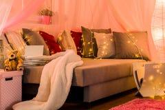 Stilvolles Bett mit dekorativer Beleuchtung Lizenzfreie Stockfotos