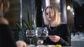 Stilvolles blondes Essen am modernen Restaurant in 4K stock footage