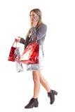 Stilvolles blondes Gehen mit Einkaufstaschen Stockbild