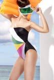 Stilvolles blondes Mädchen, das tragende Strandkleidung und Sonnenschutz aufwirft lizenzfreies stockbild