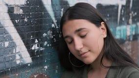 Stilvolles brunette Mädchen steht nahe der Wand mit Graffiti und traurig, ihren Kopf an der Wand lehnend stock footage