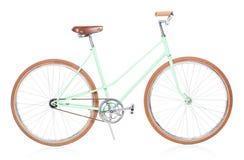 Stilvolles grünes weibliches Fahrrad mit braunen Rädern auf Weiß Stockfotografie