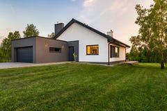 Stilvolles Haus mit großem Rasen lizenzfreie stockfotografie
