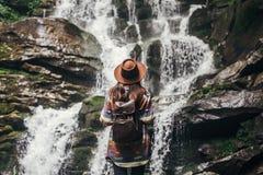 Stilvolles Hippie-Mädchen im Hut mit dem Rucksack, der Wasserfall I betrachtet stockfotos