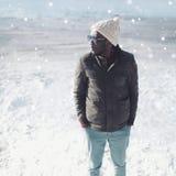Stilvolles junges afrikanisches Manntragen des Wintermodeporträts Sonnenbrille, Strickmütze und Jacke über Schnee Lizenzfreie Stockfotografie