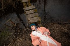 Stilvolles junges Mädchen, das auf dem Flussufer, liegend auf einer kleinen Holzbrücke stillsteht stockfotografie