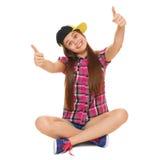 Stilvolles junges Mädchen, das Daumen oben in einer Kappe, in einem Hemd und in den Denimkurzen hosen zeigt Straßenartjugendliche Stockfoto