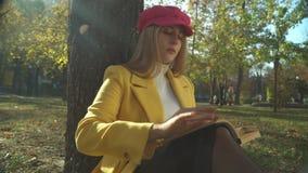 Stilvolles junges Mädchen, das ein Buch im Park liest stock footage