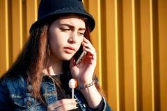 Stilvolles junges Mädchen im Hut, in den Rockschuhen und in der Denimjacke mit Dose Stockbild