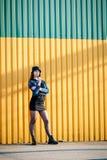Stilvolles junges Mädchen mit Hut-, Stiefel-, Rock- und Denimjacke mit Stockbild