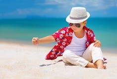 Stilvolles Kind, Junge, der mit Sand auf Sommerstrand spielt Lizenzfreie Stockfotos