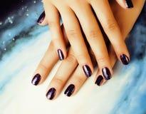 Stilvolles Konzept der Maniküre: Frauenfinger mit purpurrotem Funkeln der Nägel auf Nägeln mögen Kosmos, Universumhintergrund stockbild