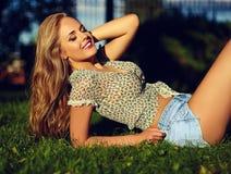 Stilvolles lächelndes Mädchen im hellen zufälligen Stoff in der kurzen Jeanshose draußen Stockbild