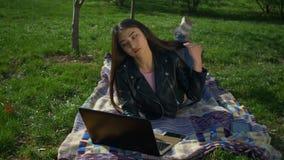 Stilvolles Mädchen, das auf dem Rasen schreibt am Laptop im Park liegt stock footage