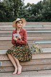 Stilvolles Mädchen, das ein Buch liest Eine Schönheit mit einem Hut, der auf Treppe eines Baums sitzt Ein Student liest ein Buch lizenzfreie stockbilder