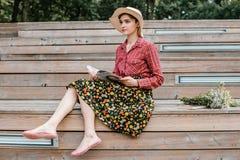 Stilvolles Mädchen, das ein Buch liest Eine Schönheit mit einem Hut, der auf Treppe eines Baums sitzt Ein Student liest ein Buch stockbild