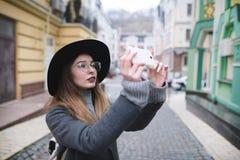 Stilvolles Mädchen, das ein Straßenfoto am Telefon fotografiert Ein touristisches Mädchen macht ein Foto von der Architektur auf  Stockfotos