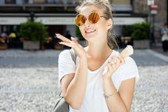 Stilvolles Mädchen, das Eiscreme isst lizenzfreie stockbilder