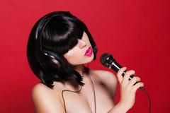 Stilvolles Mädchen, das mit einem Mikrofon, roter Hintergrund singt Stockbild