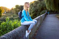 Stilvolles Mädchen, das mit einem Rucksack sitzt lizenzfreie stockbilder