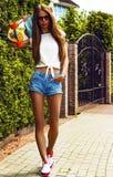 Stilvolles Mädchen in den Sonnenbrillehaltungen mit longboard Stockfoto