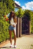 Stilvolles Mädchen in den Sonnenbrillehaltungen mit longboard Stockfotografie