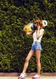 Stilvolles Mädchen in den Sonnenbrillehaltungen mit longboard Lizenzfreie Stockfotografie
