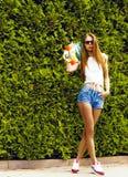 Stilvolles Mädchen in den Sonnenbrillehaltungen mit longboard Lizenzfreie Stockfotos