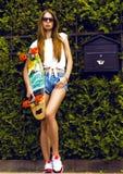 Stilvolles Mädchen in den Sonnenbrillehaltungen mit longboard Stockbild