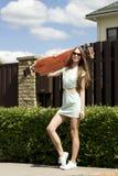 Stilvolles Mädchen in den Sonnenbrillehaltungen mit longboard Lizenzfreies Stockfoto