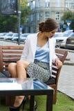 Stilvolles Mädchen der Mode, das auf der Bank sitzt Lizenzfreies Stockfoto