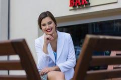 Stilvolles Mädchen der Mode, das auf der Bank sitzt Stockfotografie