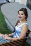 Stilvolles Mädchen der Mode, das auf der Bank sitzt Stockfotos