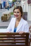 Stilvolles Mädchen der Mode, das auf der Bank sitzt Stockbilder