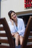 Stilvolles Mädchen der Mode, das auf der Bank sitzt Lizenzfreies Stockbild