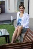 Stilvolles Mädchen der Mode, das auf der Bank sitzt Stockbild