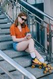 stilvolles Mädchen in der Sonnenbrille und in Rollschuhen, die auf Treppe und hörender Musik sitzen stockfotos