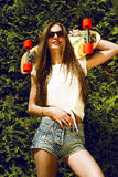 Stilvolles Mädchen in der Sonnenbrille wirft mit longboard herein auf Stockfotos