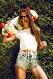Stilvolles Mädchen in der Sonnenbrille wirft mit longboard von auf Lizenzfreie Stockfotografie