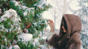 Stilvolles Mädchen des Brunette nahe Schnee bedeckte Bäume im Winter, in der braunen Pelzmantelzeitlupe stock video