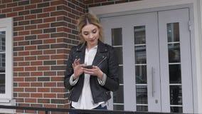Stilvolles Mädchen des Stadtlebensstils, das ein Telefon simst auf Smartphone-APP in einer Straße verwendet Blond stock footage