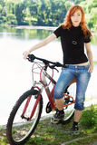 Stilvolles Mädchen draußen mit ihrem Fahrrad Stockfotografie