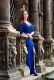 Stilvolles Mädchen in einem blauen Kleid, das nahe bei guter alter Wand steht Stockfotografie