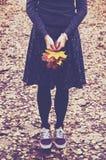 Stilvolles Mädchen mit Ahornblattbündel im Rock und in den Turnschuhen Stockfotografie