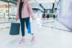 Stilvolles Mädchen mit dem Einkaufen in ihren Händen geht durch ein modernes, schönes Einkaufszentrum Das Mädchen kauft lizenzfreies stockfoto