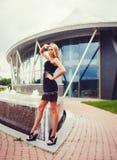 Stilvolles Mädchen mit den langen Beinen, die an der Sommerstadt aufwerfen stockbild