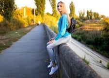 Stilvolles Mädchen mit einem Rucksacksitzen lizenzfreie stockfotos