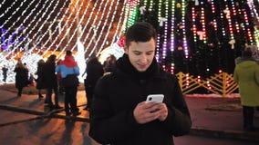 Stilvolles Manngebrauchs-Telefon mobiler App auf Heiliger Nacht auf der Straße verziert zur Partei des neuen Jahres stock video footage